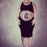 Red roses tattoo model baby bump
